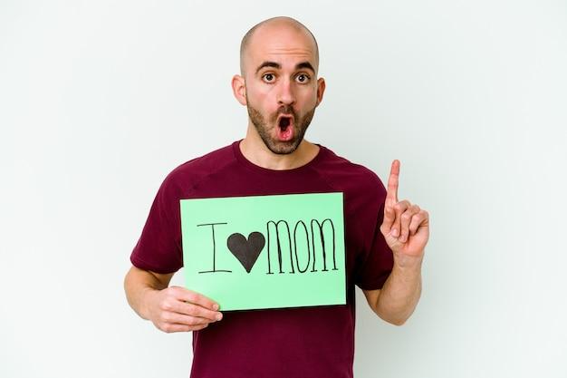 Giovane uomo calvo caucasico che tiene un cartello di i love mom isolato sulla parete gialla che ha una grande idea, il concetto di creatività.