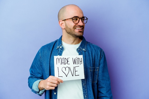 Il giovane uomo calvo caucasico che tiene un cartello fatto con amore isolato su sfondo viola guarda da parte sorridente, allegro e piacevole.
