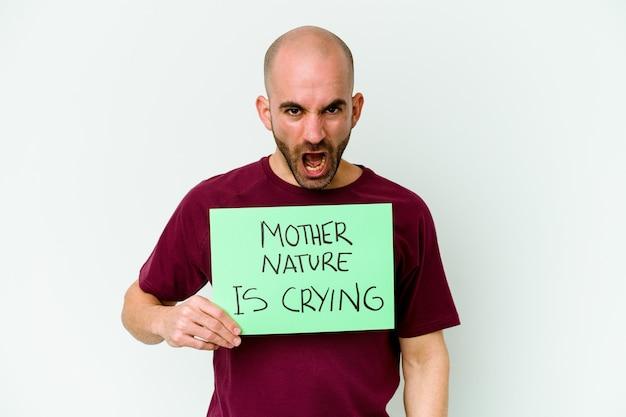 Giovane uomo calvo caucasico che tiene in mano un pianto di madre natura isolato su sfondo bianco che urla molto arrabbiato e aggressivo.
