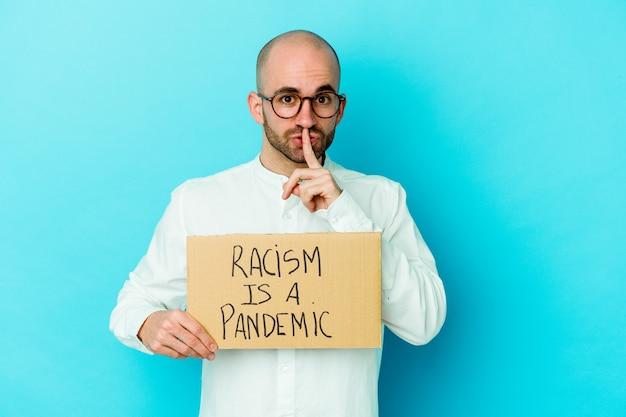 Il giovane uomo calvo caucasico che tiene un razzismo è una pandemia isolata su fondo bianco che mantiene un segreto o chiede il silenzio.