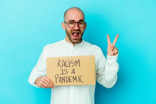 Il giovane uomo calvo caucasico che tiene un razzismo è una pandemia isolata sul muro bianco gioiosa e spensierata che mostra un simbolo di pace con le dita