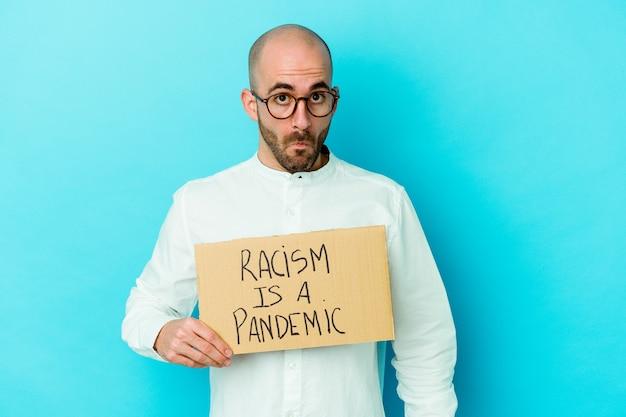 Il giovane uomo calvo caucasico che tiene un razzismo è una pandemia isolata sul muro bianco alza le spalle e apre gli occhi confusi.