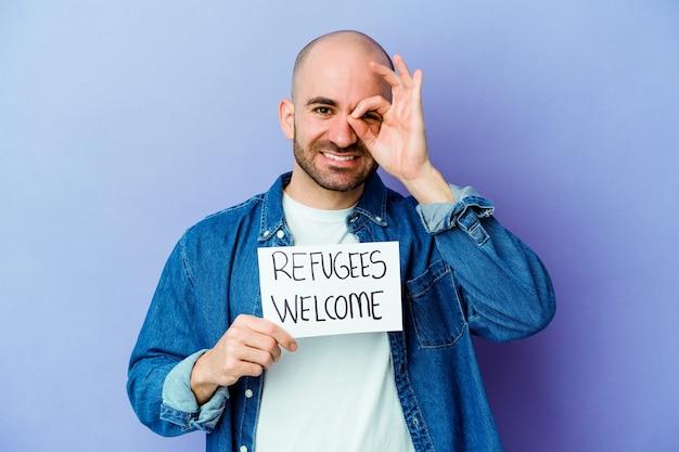 Il giovane uomo calvo caucasico che tiene un cartello di benvenuto dei rifugiati isolato su priorità bassa blu ha eccitato mantenendo il gesto giusto sull'occhio.
