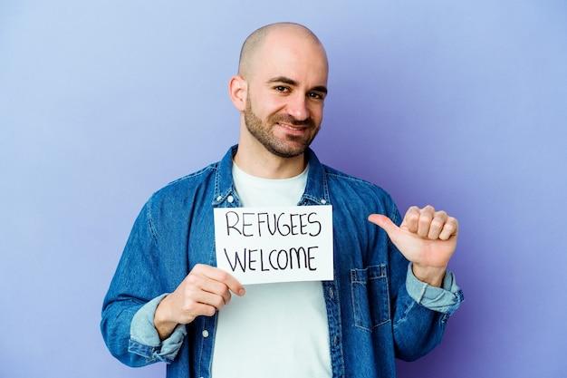 Il giovane uomo calvo caucasico che tiene un cartello di benvenuto dei rifugiati isolato su priorità bassa blu si sente orgoglioso e sicuro di sé, esempio da seguire.