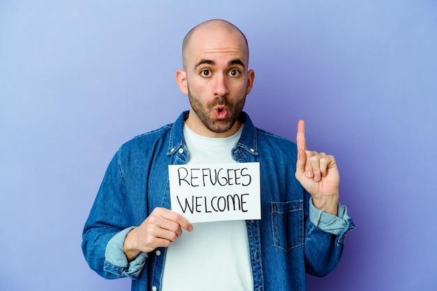 Giovane uomo calvo caucasico che tiene un cartello di benvenuto dei rifugiati isolato sulla parete blu che ha qualche grande idea, concetto di creatività.