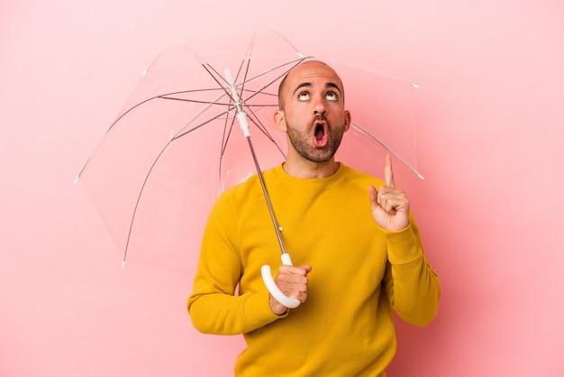Giovane uomo calvo caucasico che tiene ombrello isolato su sfondo rosa rivolto verso l'alto con la bocca aperta.