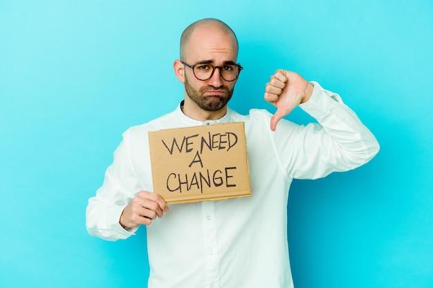 Giovane uomo calvo caucasico che tiene un abbiamo bisogno di un cartello di cambiamento isolato su sfondo viola che mostra un gesto di avversione, i pollici verso il basso. concetto di disaccordo.