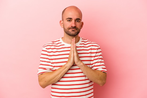 Giovane uomo calvo caucasico isolato su sfondo rosa che prega, mostra devozione, persona religiosa in cerca di ispirazione divina.