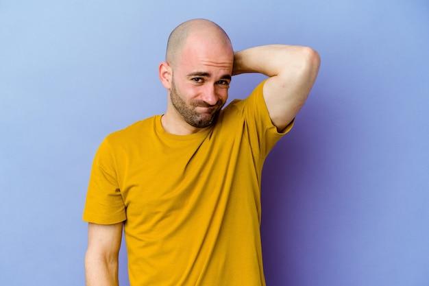 Giovane uomo calvo caucasico isolato sulla parete viola che soffre di dolore al collo a causa dello stile di vita sedentario.