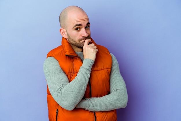 Giovane uomo calvo caucasico isolato sulla parete viola infelice alla ricerca con espressione sarcastica.