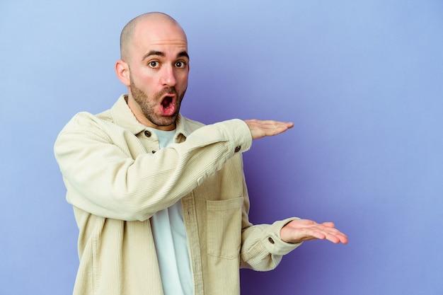 Giovane uomo calvo caucasico su viola scioccato e stupito in possesso di uno spazio di copia tra le mani.