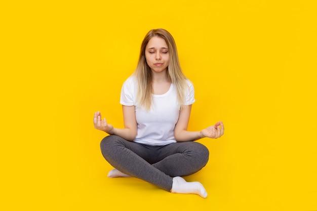 Una giovane bella donna bionda caucasica in una maglietta bianca e leggings grigi seduta nella posizione del loto meditando isolata su un muro giallo di colore brillante