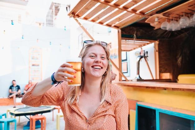 Giovane donna bionda caucasica felice per una celebrazione e bere un bicchiere di birra