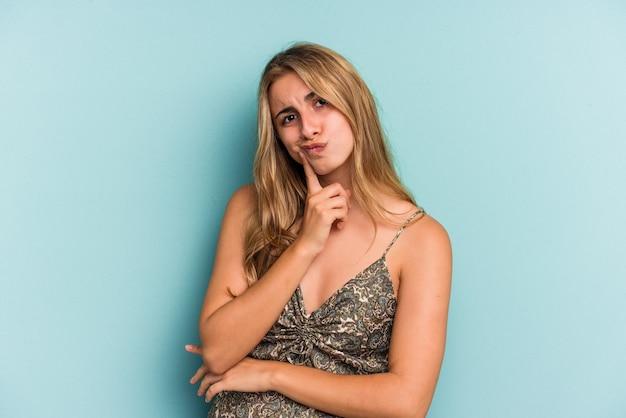 Giovane donna bionda caucasica isolata su sfondo blu contemplando, pianificando una strategia, pensando al modo di fare affari.