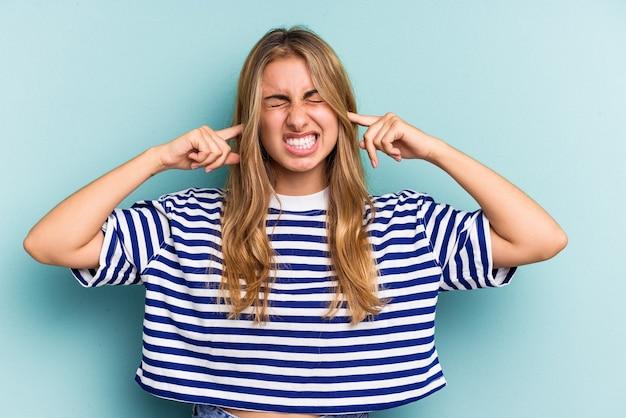 Giovane donna bionda caucasica isolata su sfondo blu che copre le orecchie con le dita, stressata e disperata da un ambiente rumoroso.