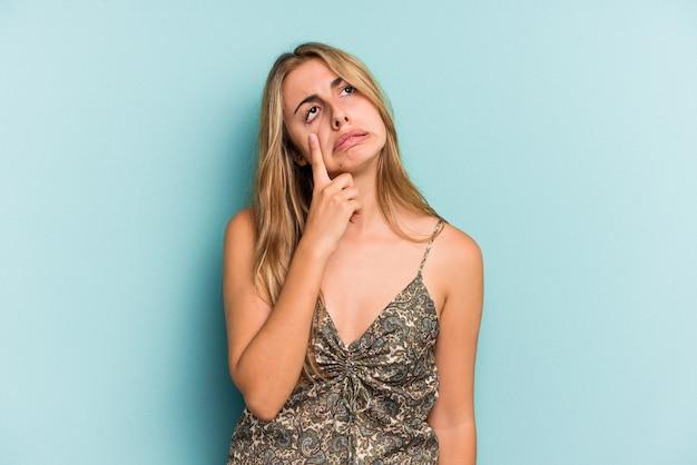 Giovane donna bionda caucasica isolata su sfondo blu che piange, infelice con qualcosa, agonia e concetto di confusione.