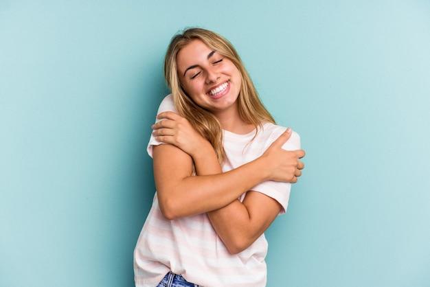 La giovane donna bionda caucasica isolata sugli abbracci blu del fondo, sorride spensierata e felice.