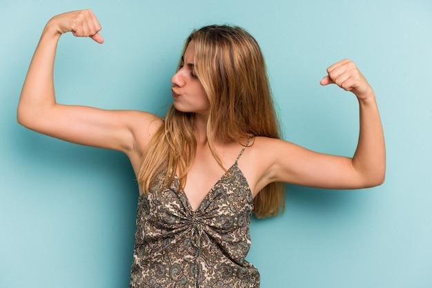Giovane donna bionda caucasica isolata su sfondo blu che mostra un gesto di forza con le braccia, simbolo del potere femminile