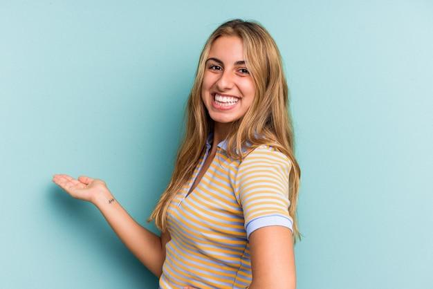 Giovane donna bionda caucasica isolata su sfondo blu che mostra un'espressione di benvenuto.