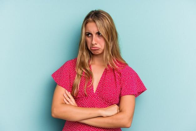 Giovane donna bionda caucasica isolata su sfondo blu stanca di un compito ripetitivo.