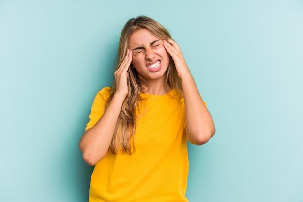 Giovane donna bionda caucasica isolata su sfondo blu toccando le tempie e avendo mal di testa.