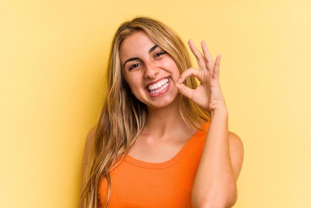 Giovane donna bionda caucasica isolata su sfondo giallo allegro e fiducioso che mostra gesto ok.