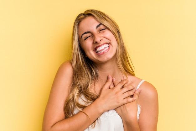 La giovane donna bionda caucasica isolata su sfondo giallo ha un'espressione amichevole, premendo il palmo sul petto. concetto di amore.
