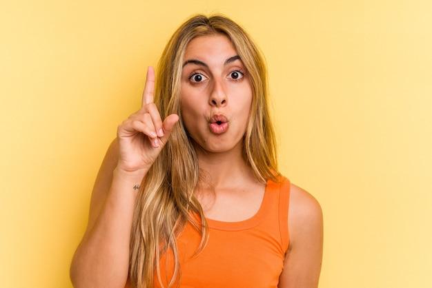 Giovane donna bionda caucasica isolata su sfondo giallo con qualche grande idea, concetto di creatività.