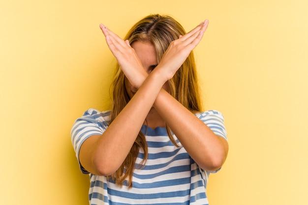 Giovane donna bionda caucasica isolata su sfondo giallo mantenendo due braccia incrociate, concetto di negazione.
