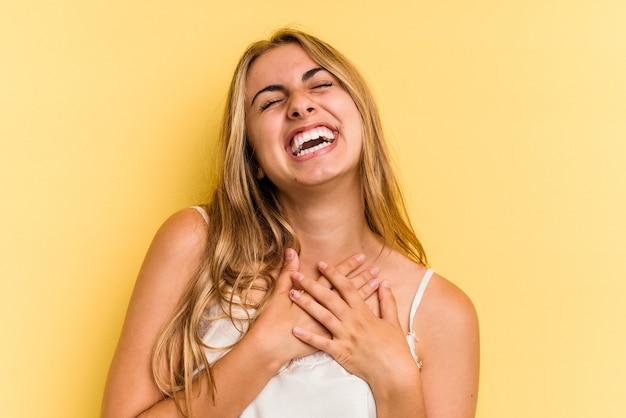 Giovane donna bionda caucasica isolata su sfondo giallo ride forte tenendo la mano sul petto.