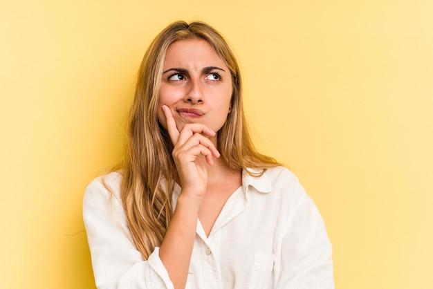Giovane donna bionda caucasica isolata su sfondo giallo guardando lateralmente con espressione dubbiosa e scettica.
