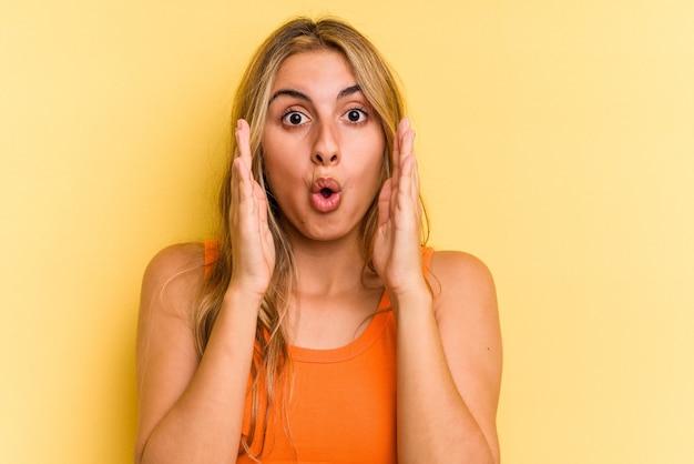 Giovane donna bionda caucasica isolata su sfondo giallo sorpresa e scioccata.