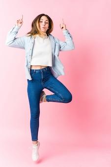 Giovane donna bionda caucasica che salta sulla parete rosa