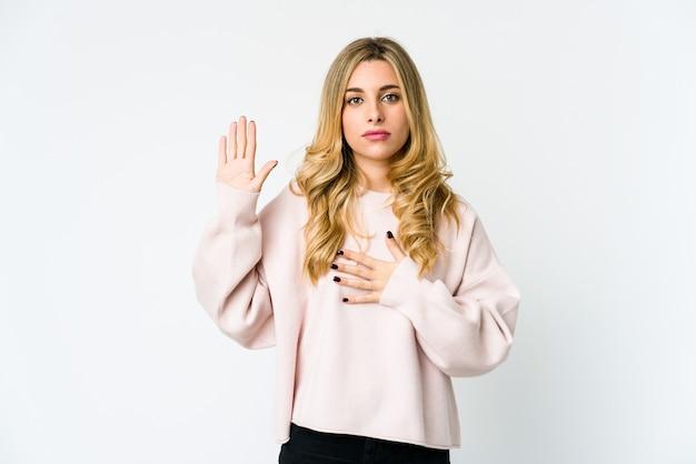 Giovane donna bionda caucasica prestando giuramento, mettendo la mano sul petto.