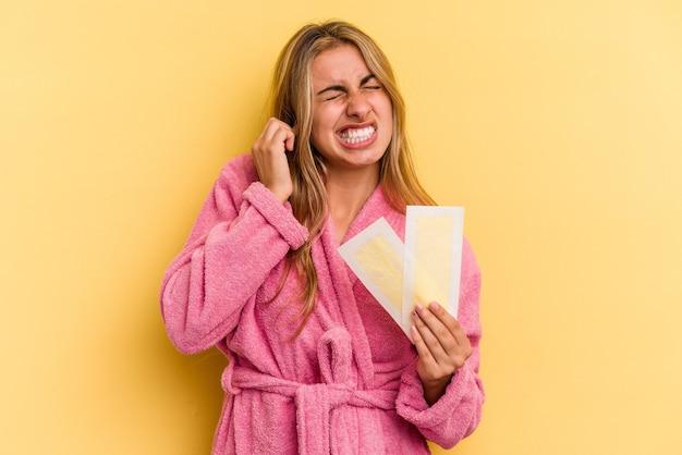 Giovane donna bionda caucasica che indossa accappatoio che tiene fasce depilatorie isolate su sfondo giallo che copre le orecchie con le mani.