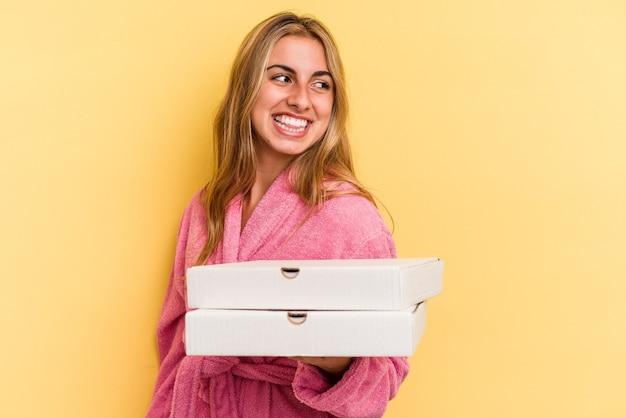 La giovane donna bionda caucasica che indossa l'accappatoio che tiene le pizze isolate su fondo giallo guarda da parte sorridente, allegra e piacevole.