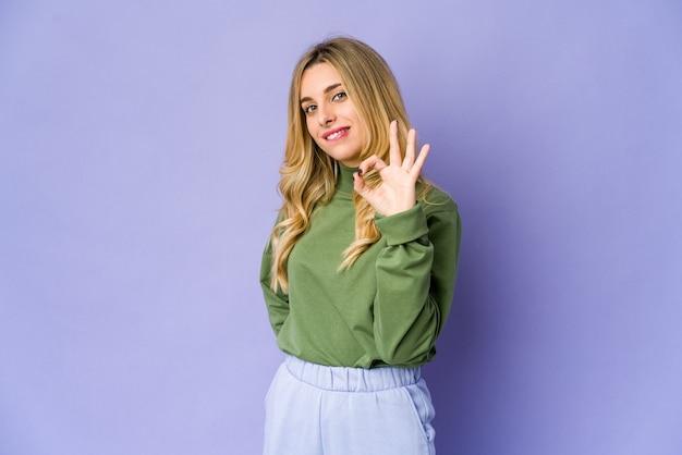 La giovane donna bionda caucasica strizza l'occhio e tiene un gesto giusto con la mano.