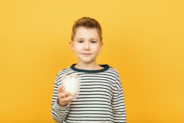 Giovane ragazzo caucasico che tiene un bicchiere di latte isolato