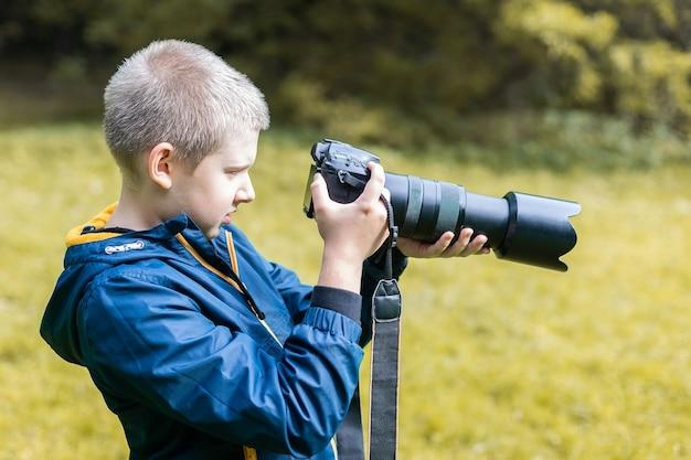 Giovane ragazzo caucasico che cattura un tiro con la sua fotocamera dslr. ambiente naturale.