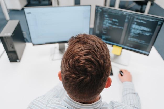Giovane ragazzo caucasico che lavora come scienziato informatico durante la lettura del codice