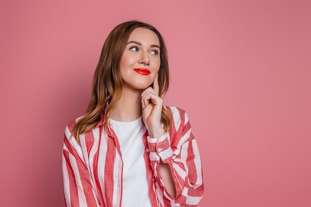 Giovane donna bruna caucasica pensando e distogliendo lo sguardo isolato sulla parete rosa