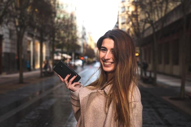 Giovane donna bruna caucasica utilizzando uno smartphone in strada