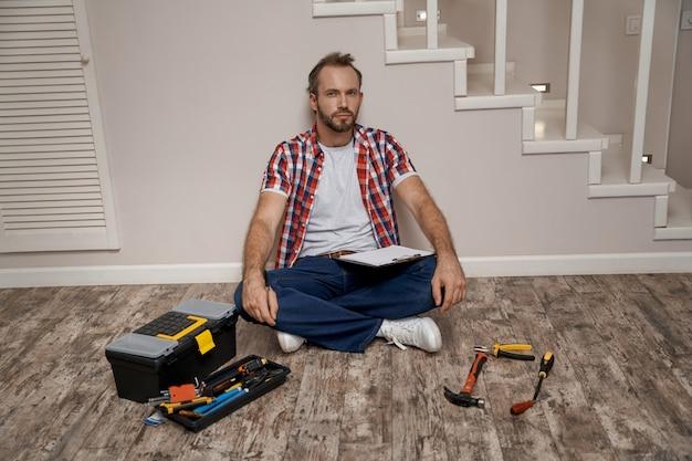 Giovane costruttore caucasico seduto sul pavimento vicino agli strumenti di riparazione