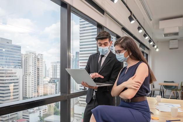 Giovane collega caucasico di affari che indossa la maschera per il viso discutendo con il computer portatile nel nuovo ufficio normale al quartiere degli affari
