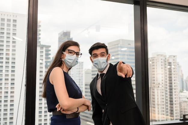 Giovane collega di affari caucasico che indossa la maschera per il viso e dito puntato in ufficio