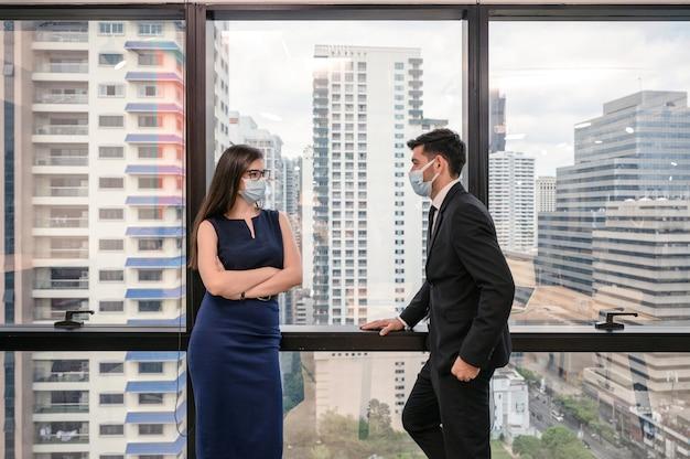 Giovane collega caucasico di affari che indossa la maschera per il viso con parlare alla finestra nel nuovo ufficio normale
