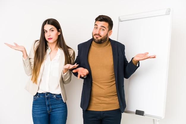 Le giovani coppie caucasiche di affari hanno isolato dubitare e scrollare le spalle le spalle nel gesto interrogante.