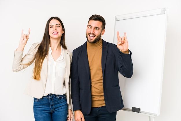 Giovani coppie caucasiche di affari isolate che mostrano un gesto di corna come un concetto di rivoluzione.