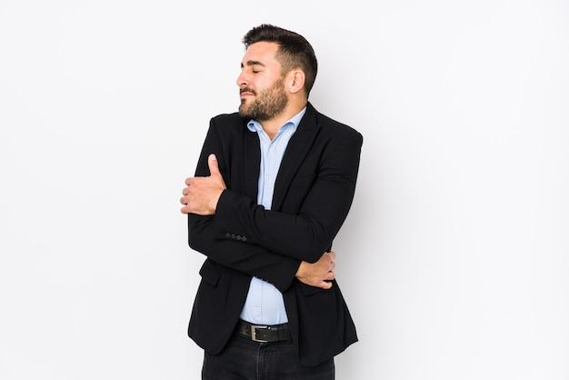 Giovane uomo d'affari caucasici contro un muro bianco abbracci, sorridente spensierato e felice.