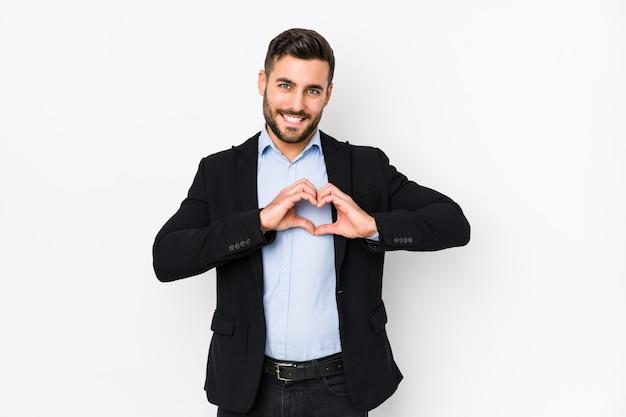 Il giovane uomo caucasico di affari contro una parete bianca ha isolato sorridere e mostrare una forma del cuore con le mani.